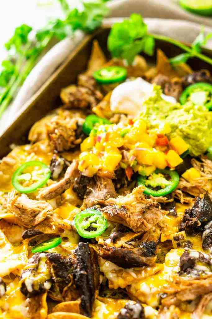 The jerk pork nachos with guacamole, sour cream and tropical pico de gallo on top and cilantro in the background.