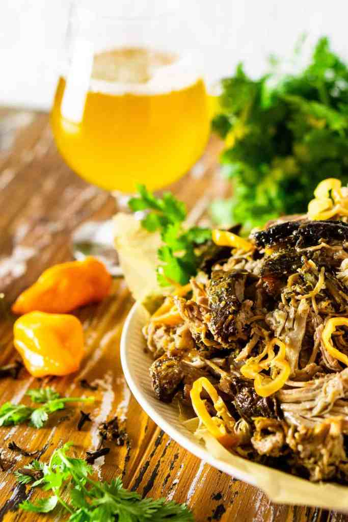 A plate of shredded jerk pork shoulder with cilantro sprigs on the side and a beer in the background.