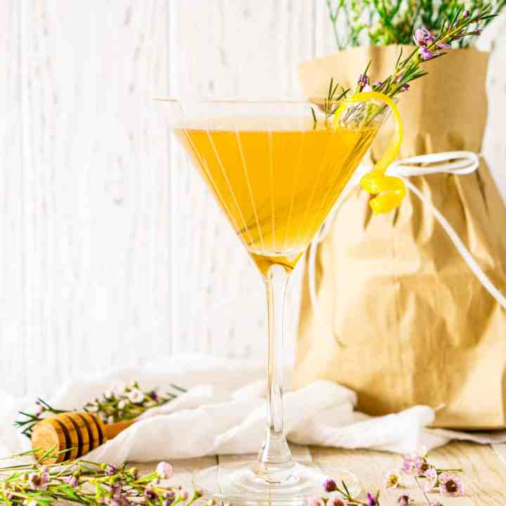 A lavender bee's knees cocktail with purple flowers scattered around it with a honey dipper in the background.