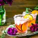 Two plum-thyme margaritas on a silver tray with a purple flower and thyme.