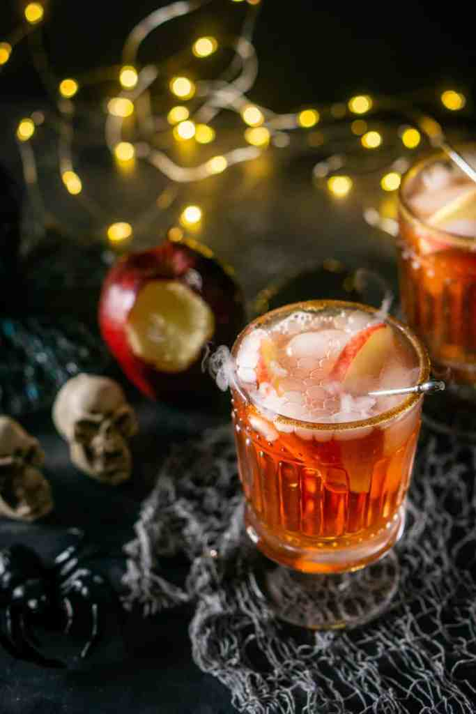 Two Poisoned Orchard Cocktails on a gray cloth with lights.