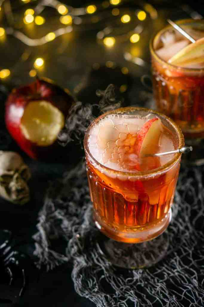 Two Poisoned Orchard Cocktails with glowing lights and a bitten apple on gray cloth.