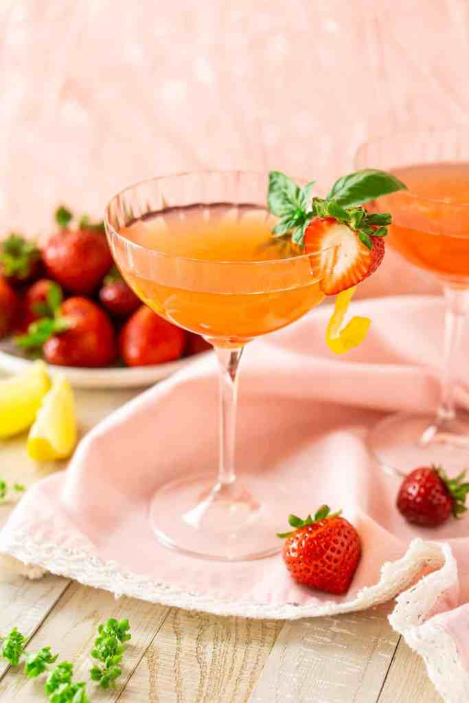 A strawberry limoncello martini with a strawberry on the side and lemon slices in the background.