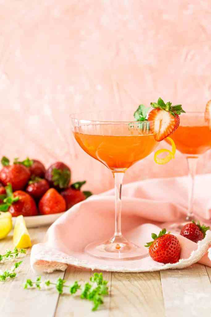 Two strawberry-basil limoncello martinis on a pink napkin with strawberries and basil flowers around it.