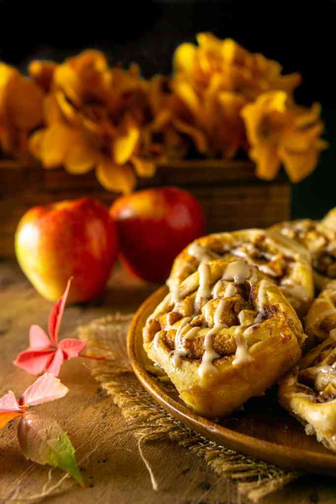 A wooden plate of apple cinnamon rolls with apple and flowers in the background.