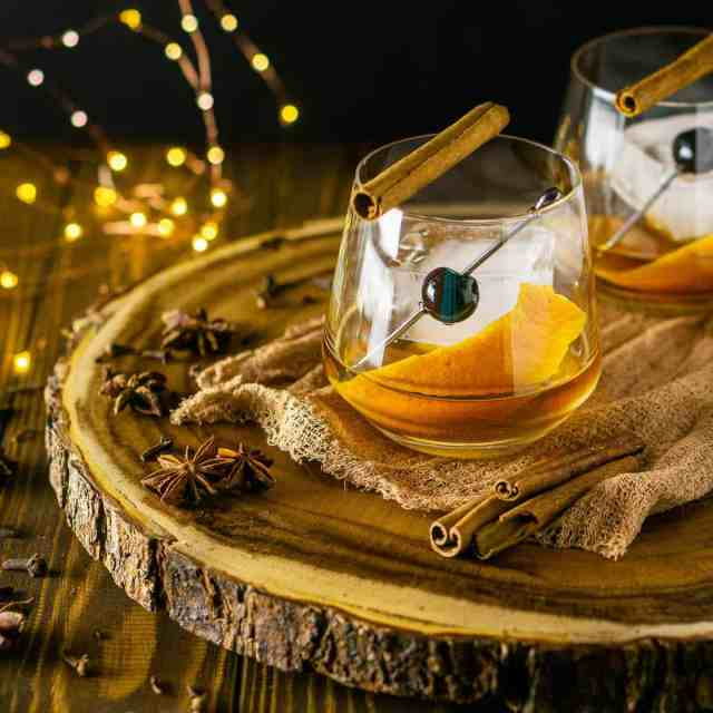 Two chai old fashioned cocktails on a wooden platter with spices on the side and lights in the background.
