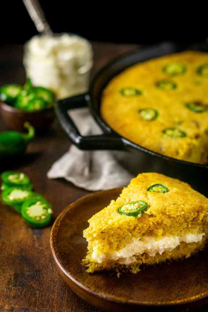 A slice of the jalapeno popper cornbread filled with the whipped cream cheese butter on a small wooden plate.