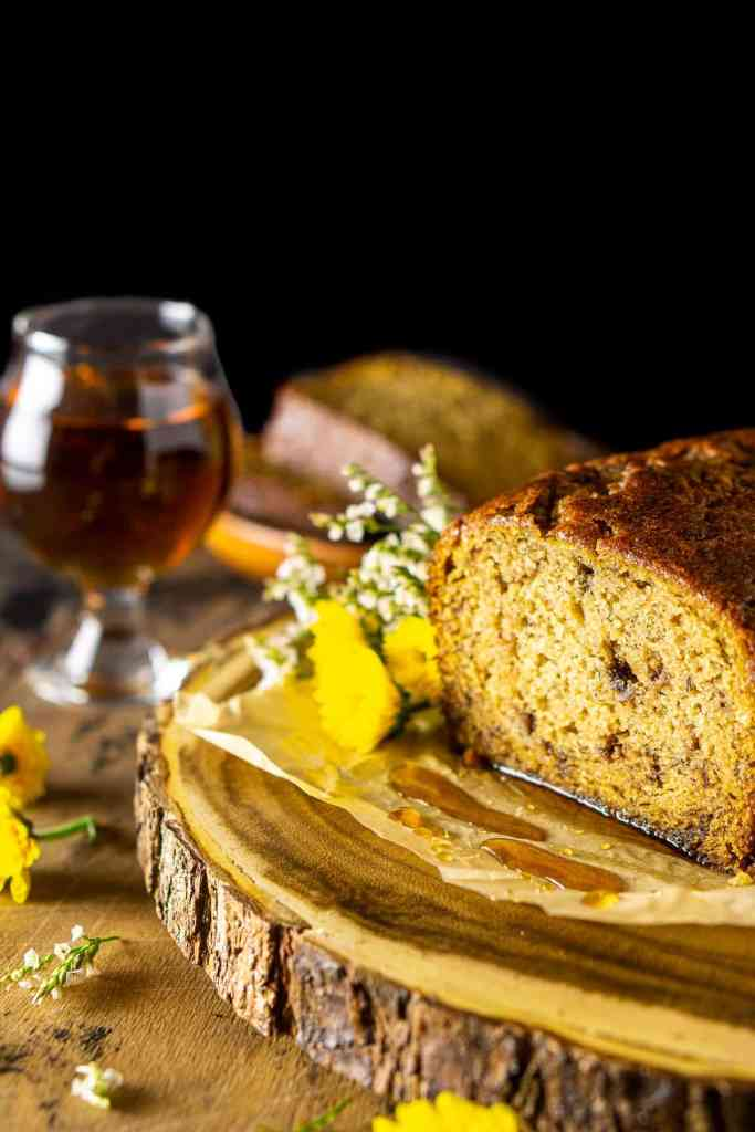 The maple-bourbon banana bread on a wooden platter with flowers to the side.