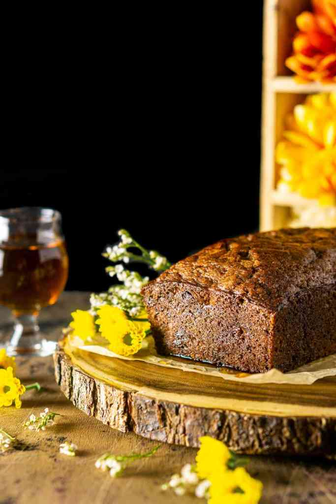 The banana bread before it's been sliced on a wooden platter with flowers all over.