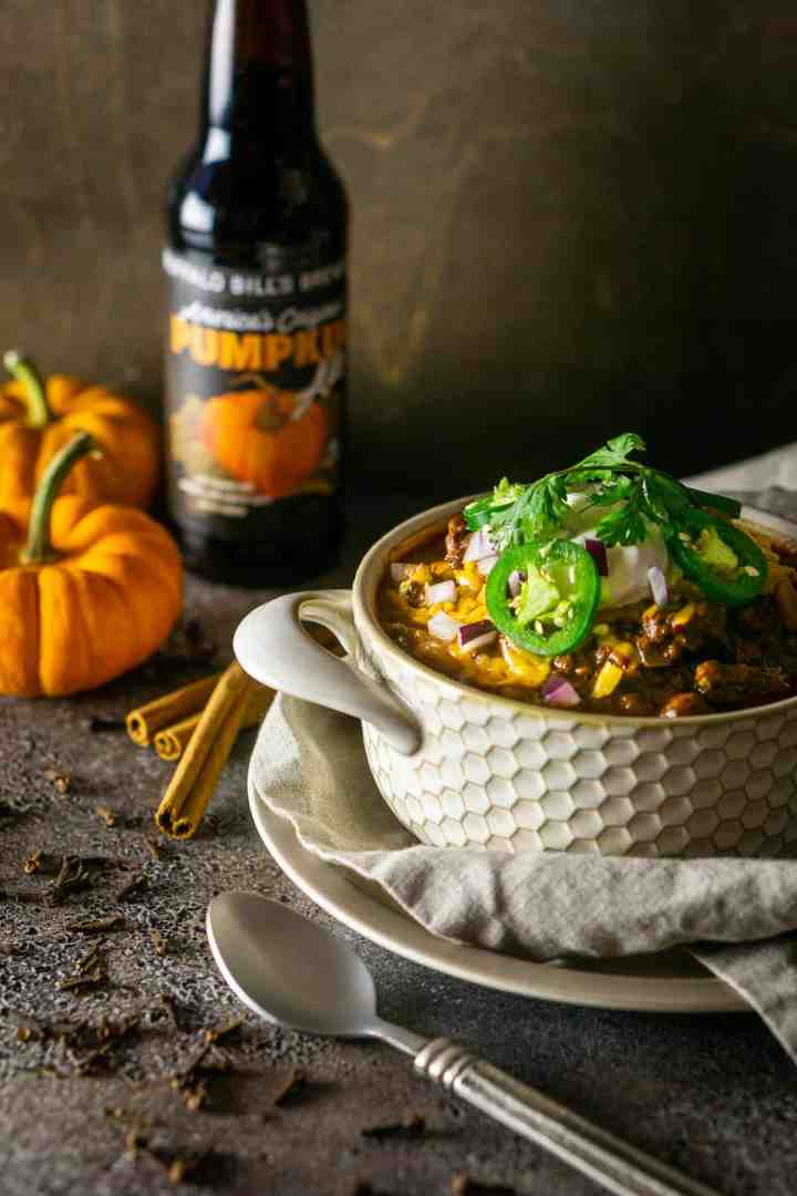 The pumpkin and chorizo chili on a small plate with a clothe napkin and a beer in the background with pumpkins.