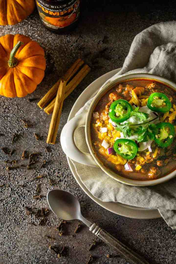 An aerial view of the pumpkin and chorizo chili with spices, a spoon, pumpkin and a beer to the side.