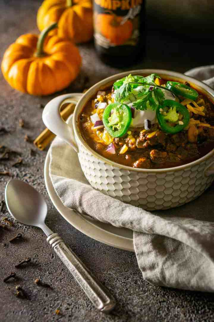 The pumpkin and chorizo chili on a plate with a spoon to the side and whole cloves surrounding it.