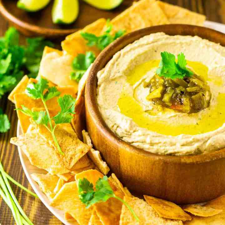 A bowl of creamy Hatch green chile hummus with pita chips on the side, lime slices in the background and pieces of fresh cilantro.