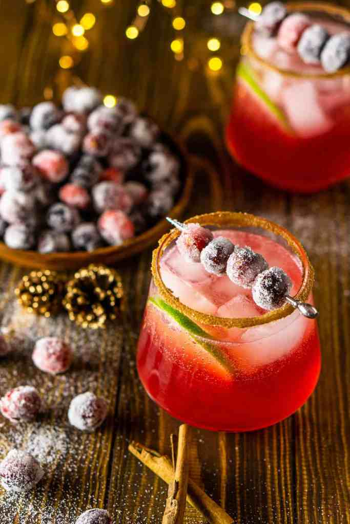 A sparkling cranberry margarita with lights and sugared cranberries on the side.