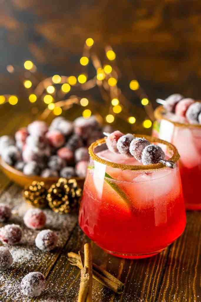 Two holiday cranberry margaritas with lights behind them.