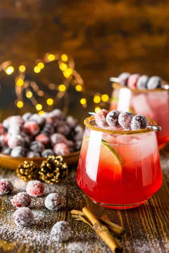 A sparkling cranberry-ginger margarita with sugared cranberries to the side and holiday lights behind it.