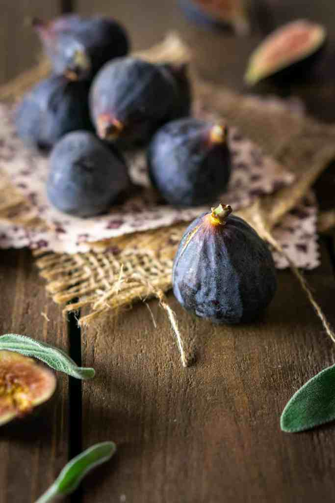A pile of fresh black mission figs on burlap with fresh sage around them.