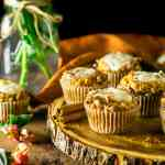 Several sweet potato muffins with ginger cream cheese filling on a wooden board with cinnamon sticks and fall flowers around them.