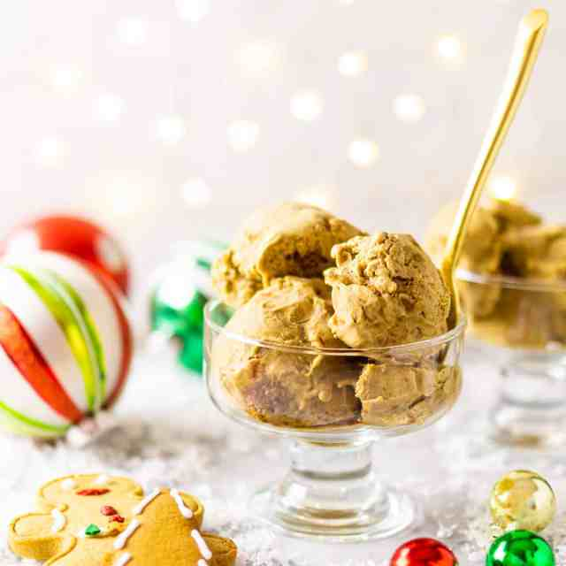 A glass bowl of gingerbread ice cream with ornaments and gingerbread cookies around it with a gold spoon sticking out of the bowl.