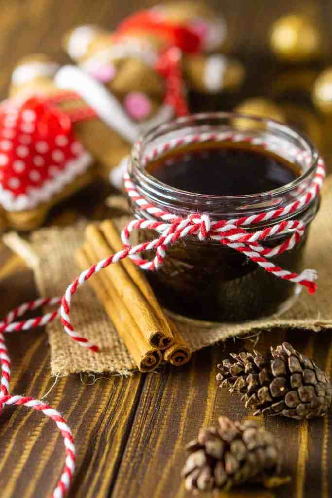 A close-up shot of the gingerbread simple syrup with Christmas decor behind it.
