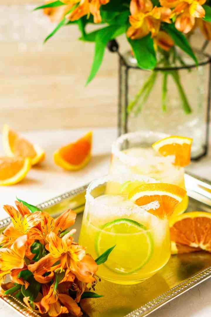 Two orange margaritas on a silver platter with flowers on the side.