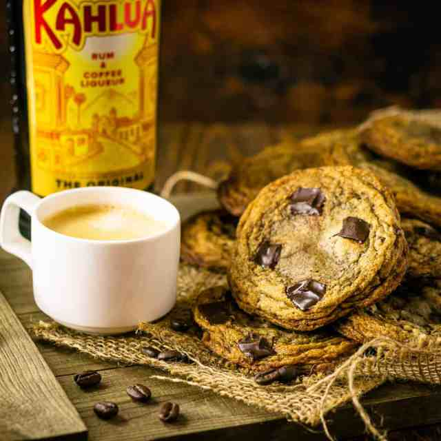 A pile of espresso and Kahlua cookies on a wooden tray with burlap and a cup of espresso and bottle of Kahlua next to it.
