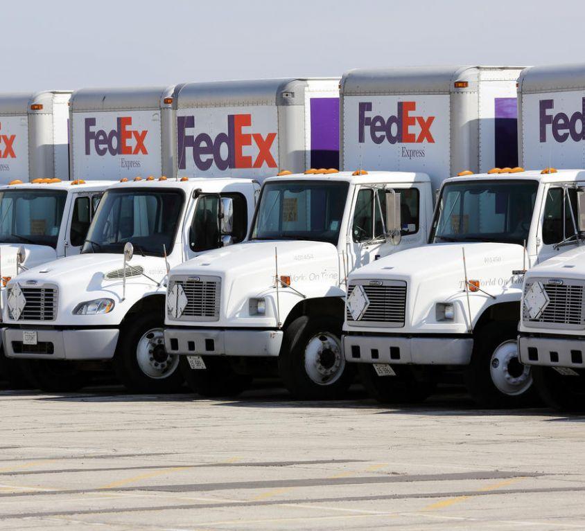 Fleet of FedEx delivery trucks in a parking lot