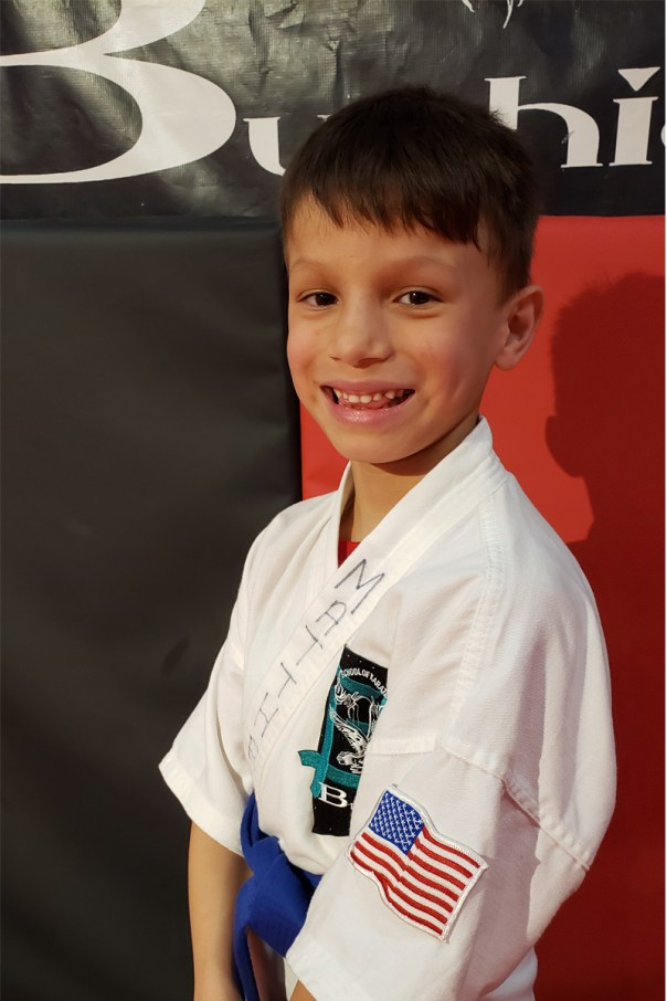 young boy in karate gi posing with smile