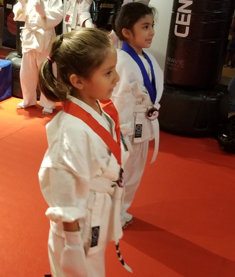 little girls getting karate medals