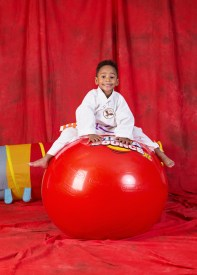 young karate student balancing on a ball