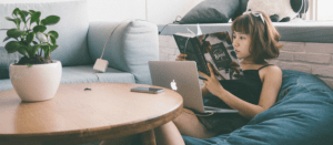 Girl lounging on cushion reading book with laptop open