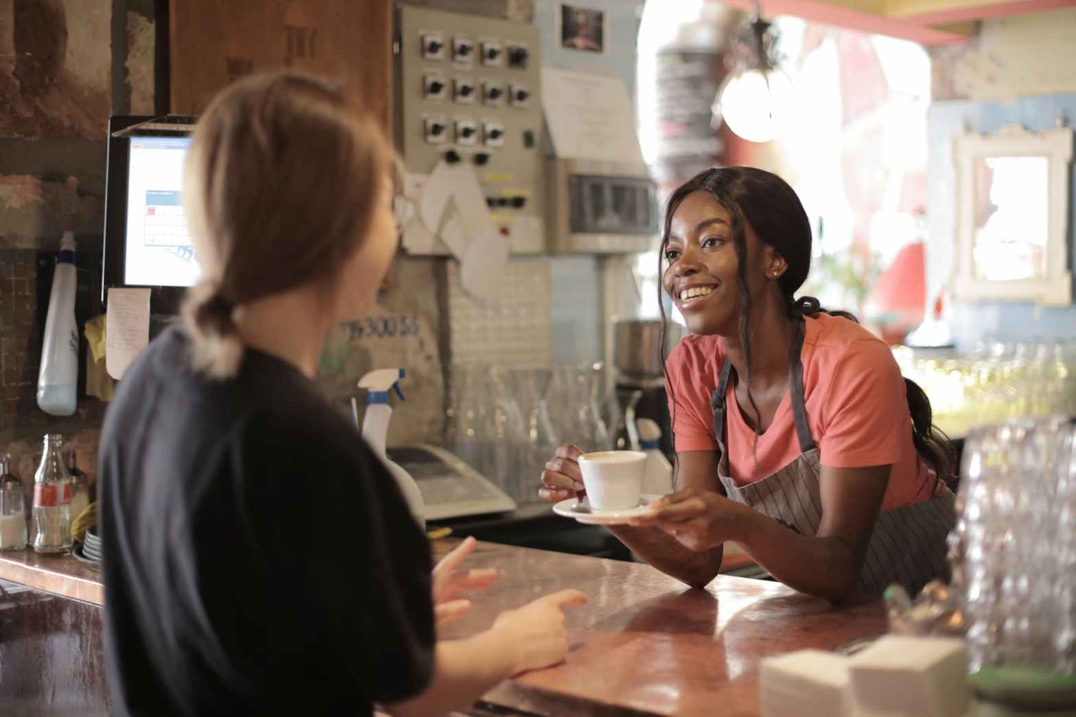 delighted black female barista serving coffee in cup in cafe. Delivering great customer service to the guest