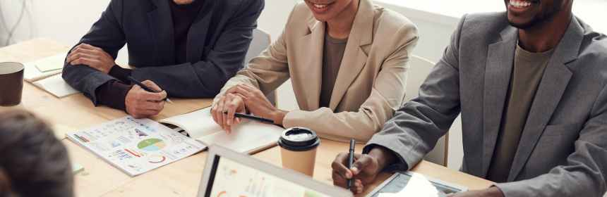 photo of three people smiling while having a meeting