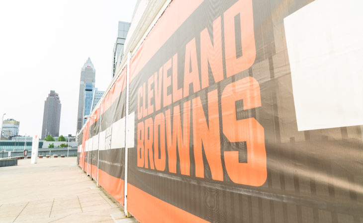Cleveland, Ohio/USA - June 1, 2019: Cleveland Brown's Banner Closeup Leading To The Structural Cityscape Skyline Of Downtown Cleveland.