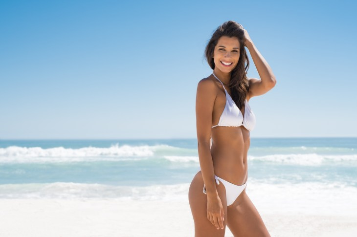 Portrait of young woman in white bikini on tropical beach looking at camera. Beautiful latin girl in swimwear with copy space. Summer vacation and tanning concept.