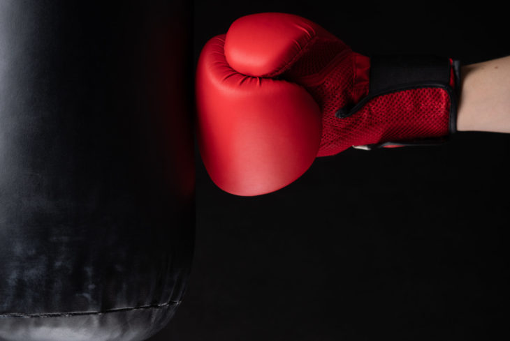 red boxing glove hitting the punching bag on black background