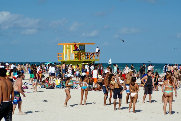 MIAMI, FLORIDA, USA - CIRCA MARCH 2016: Spring break visitors gathered around a yellow lifeguard tower on South Beach