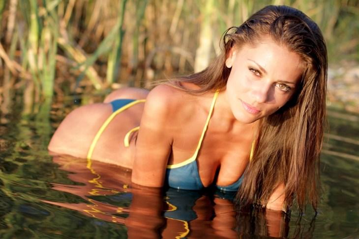 Sexy girl in bikini posing at sunset
