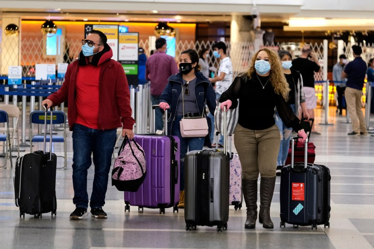 Holiday travelers wearing face masks arrive at the Los Angeles International Airport (LAX), in Los Angeles on Tuesday, Dec. 22, 2020.