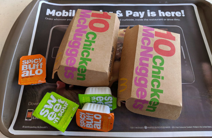 Waikiki - July 19, 2018: Two Ten Piece Chicken McNuggets on a tray with dipping sauces Spicy Buffalo and Sweet and Sour inside a McDonald's store.