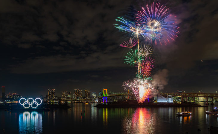 Tokyo, Japan - January, 2020: A picture of the fireworks commemorating the opening of the Olympic Rings in the Tokyo Bay, featuring the Rainbow Bridge, at night.