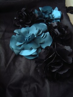Arrange the flowers onto the dress and then sew them on.
