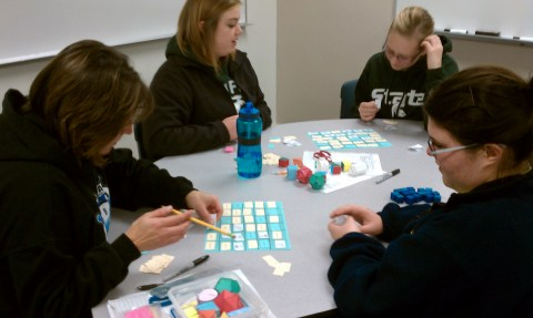 Four students playing Geometry Vocabulary Block on two game boards.