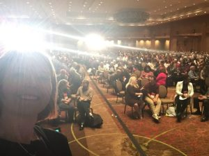 Selfie with room full of participants in the background