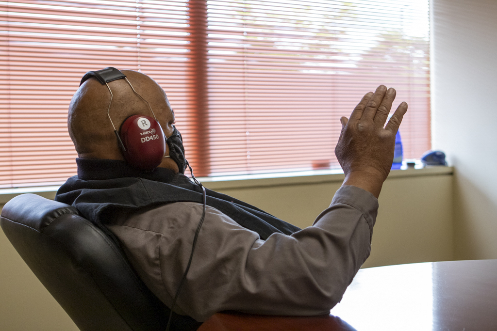 An man sits in a chair and raises his hand signaling that he can hear a tone from the headphones he is wearing in an Audiogram test.