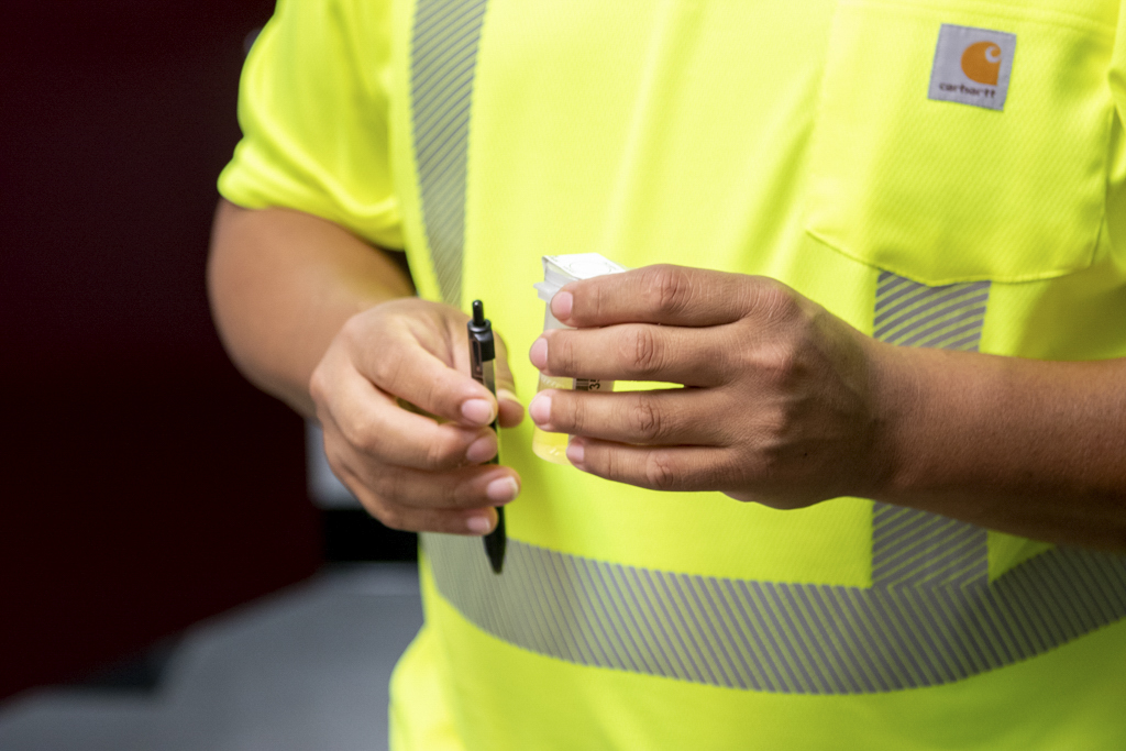 New employee sign his urine drug test vial for Butterfield Onsite Drug Testing.