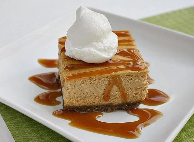Pumpkin Caramel Cheesecake Bars made with a gingersnap crust and topped with creamy pumpkin cheesecake & caramel sauce. Festive and everyone loves it!