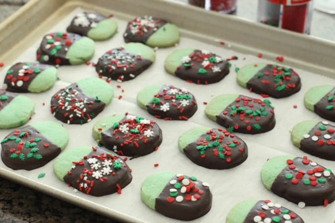 Chocolate Mint Cookies made from a buttery shortbread cookie dipped in dark chocolate & topped with festive holiday sprinkles.My favorite Christmas cookie!