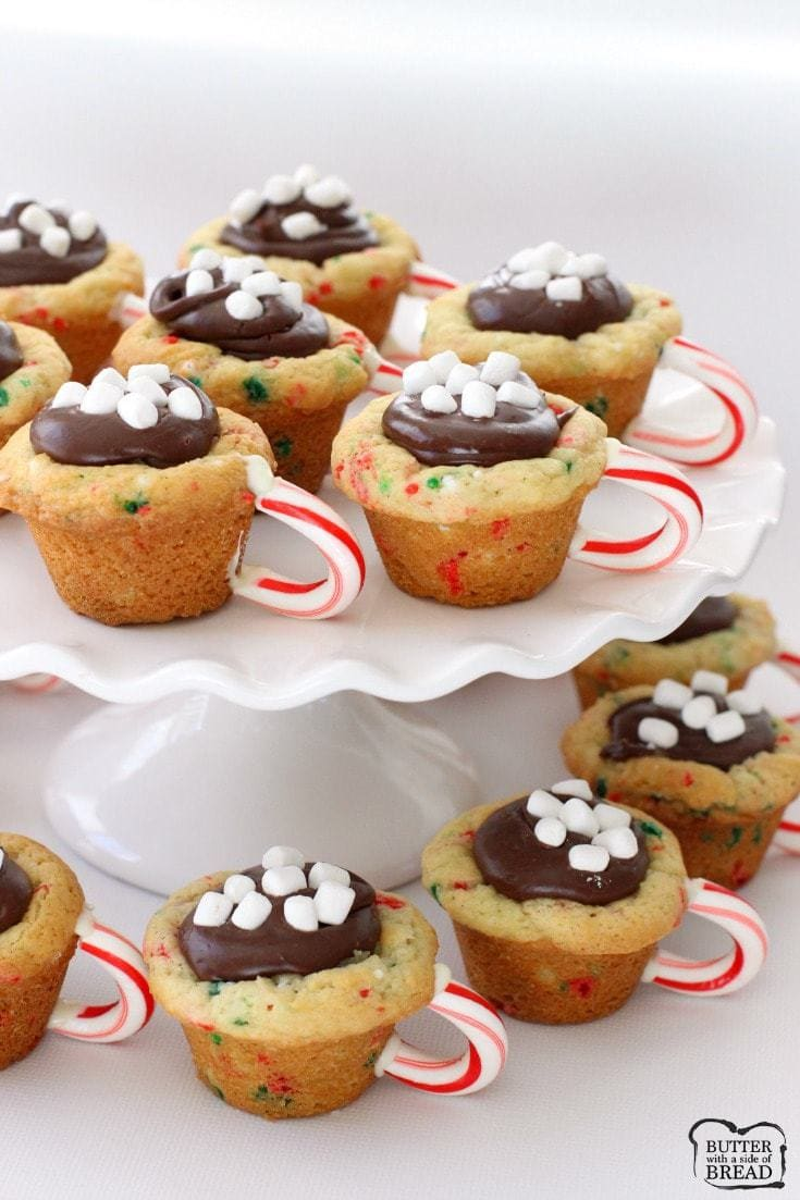 Hot Chocolate Cookie Cups are the most fun & festive Christmas cookies ever! Sugar cookie cups filled with fudge, mini marshmallows & sprinkles with a darling candy cane handle!