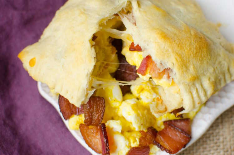 Bacon, Egg and Cheese Breakfast Pockets are full of fluffy scrambled eggs, bacon bits, and melted cheese wrapped up and baked in canned crescent roll dough. These Breakfast Pockets are both easy and delicious. Not to mention, they are freezer friendly and make a great breakfast on the go!